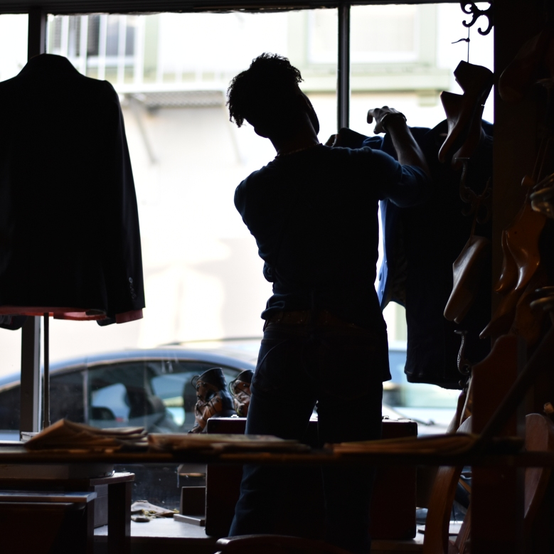 Nick Brentley adjusts the window display at Al's Attire custom tailor shop in the North Beach district of San Francisco, Calif., on Monday, Feb. 12, 2018. Brentley works as a stylist and designer at the shop.