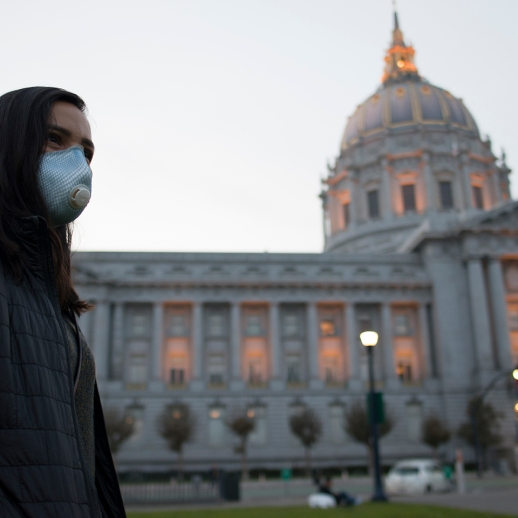 Paloma Rodriguez wears a face mask to protect herself from smoke from the Camp Fire as she waits for friends near San Francisco City Hall on November 18, 2018 (Boone Ashworth/Xpress)
