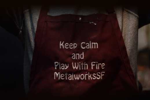 Adriana Bolotsky, a student at the Metalworks SF jewelry making school, wears an apron to protect her clothes from stray bits of molten metal as she prepares to craft a ring on Thursday, Nov. 30, 2017 in San Francisco, Calif.