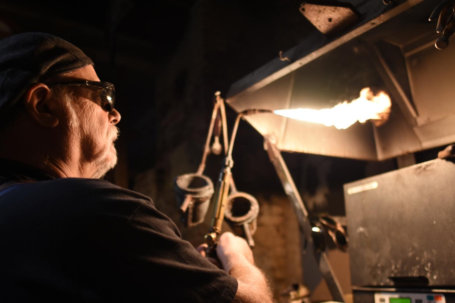 Daniel Macchiarini, owner of jewelry shop Macchiarini Creative Design, uses a propane torch to melt silver into a casting mold at his shop in San Francisco.