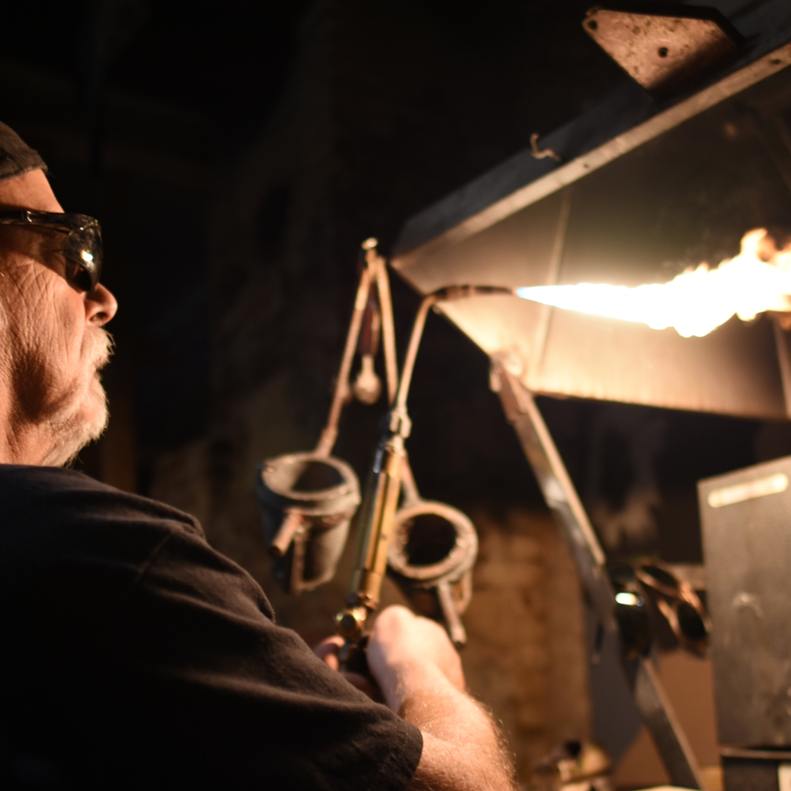 Daniel Macchiarini, owner of jewelry shop Macchiarini Creative Design, uses a propane torch to melt silver into a casting mold at his shop in San Francisco.